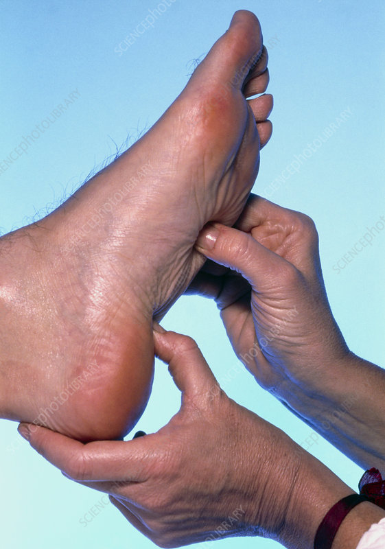 Hands of a reflexologist massaging a man's foot