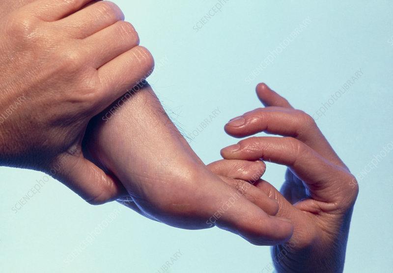 Hands of a reflexologist massaging a man's foot