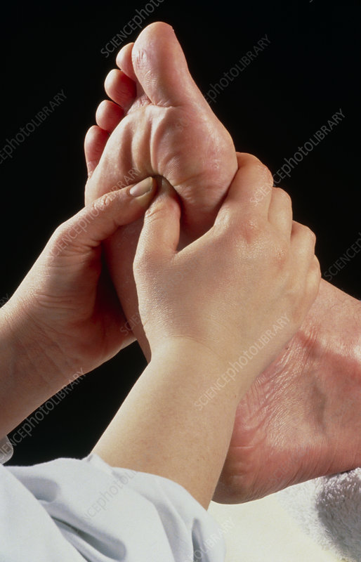 Reflexologist massaging a patient's foot