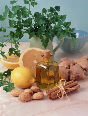 Bottle of aromatherapy oil surrounded by herbs