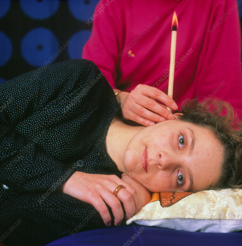 Woman being treated with a Hopi ear candle