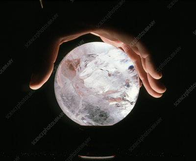 Crystal therapy: rock crystal sphere in man's hand