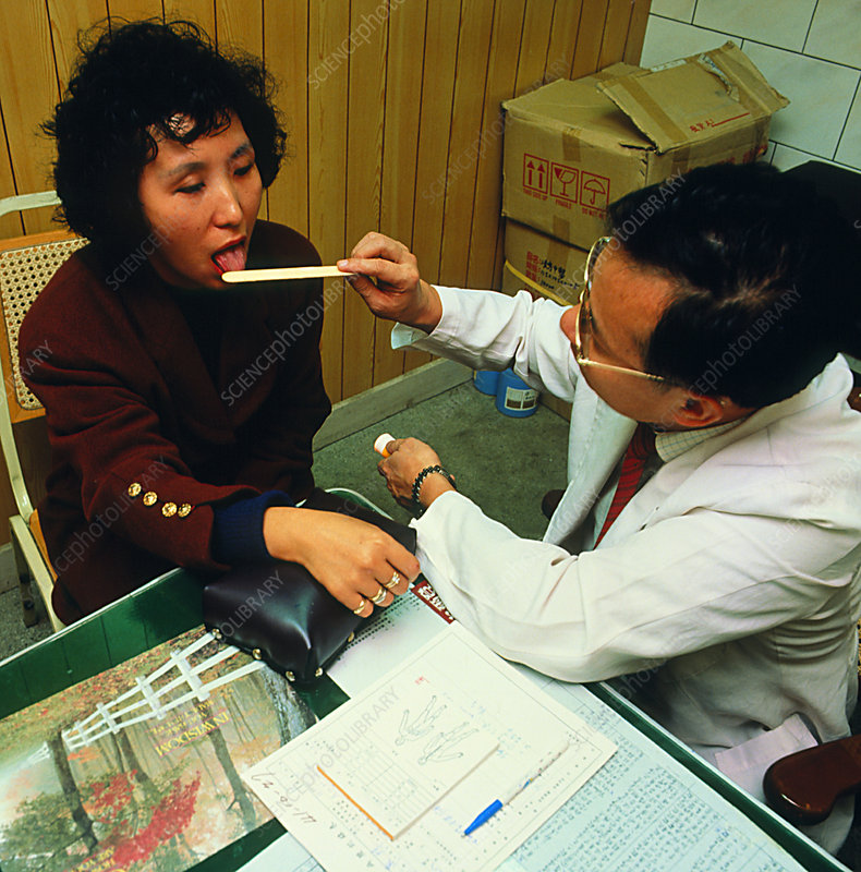 Woman having tongue examination by Chinese doctor