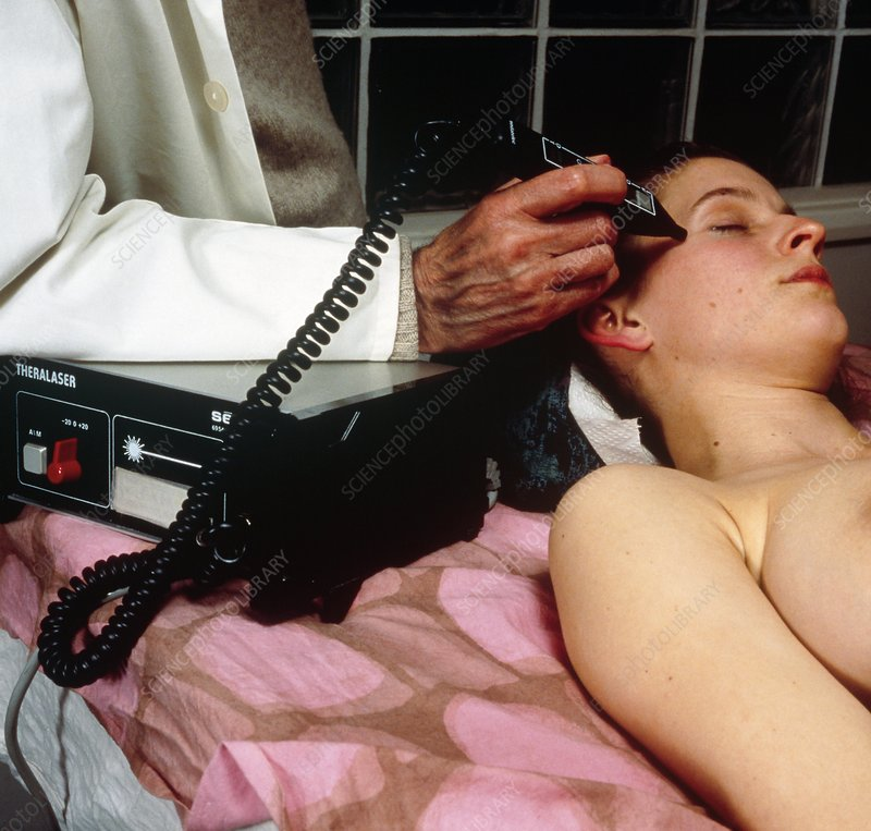 Acupuncturist using a low-powered laser unit