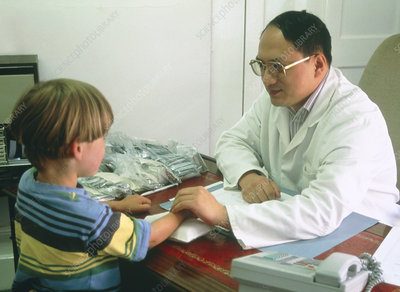 Chinese medicine practitioner takes boy's pulse