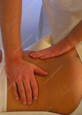 Osteopath treating the back of a patient