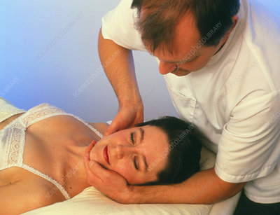 Osteopath treating the neck of a patient