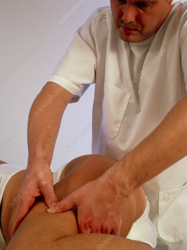 Osteopath treating the thigh of a patient