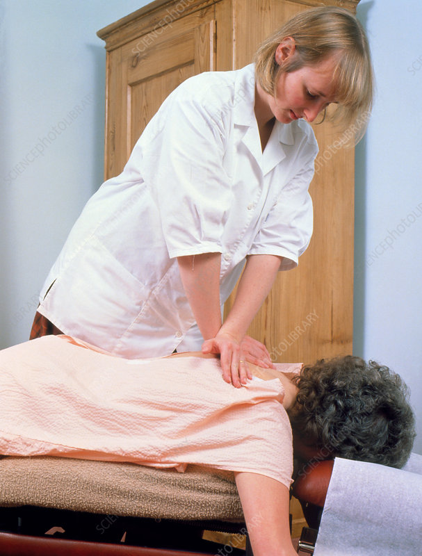 Chiropractor presses on spine of a woman patient