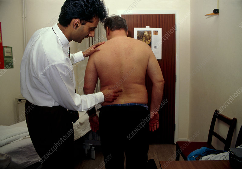 Osteopath examines the lower spine of a man