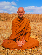 Buddhist monk meditating in a crop circle
