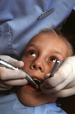 Child having a tooth drilled by a dentist