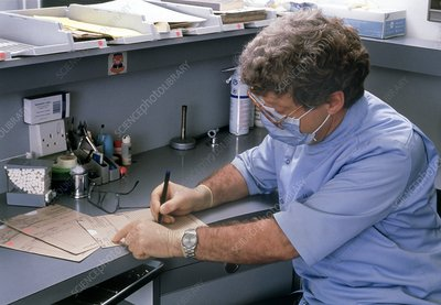Dentist writing patient's notes