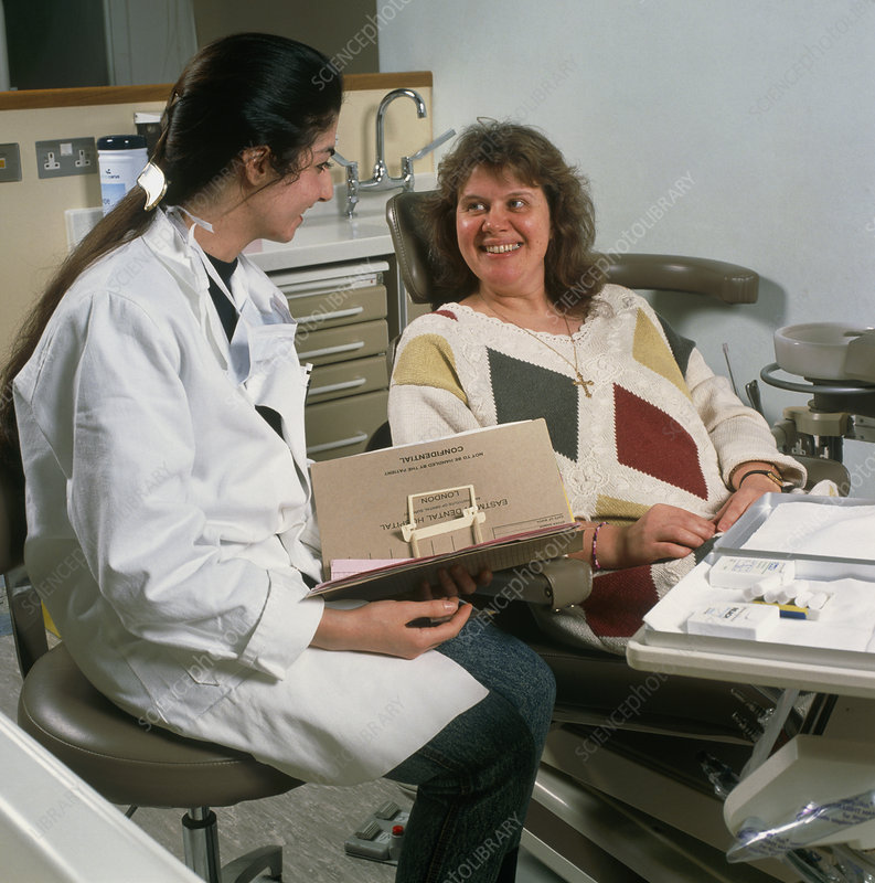 Dental hygienist consults with woman
