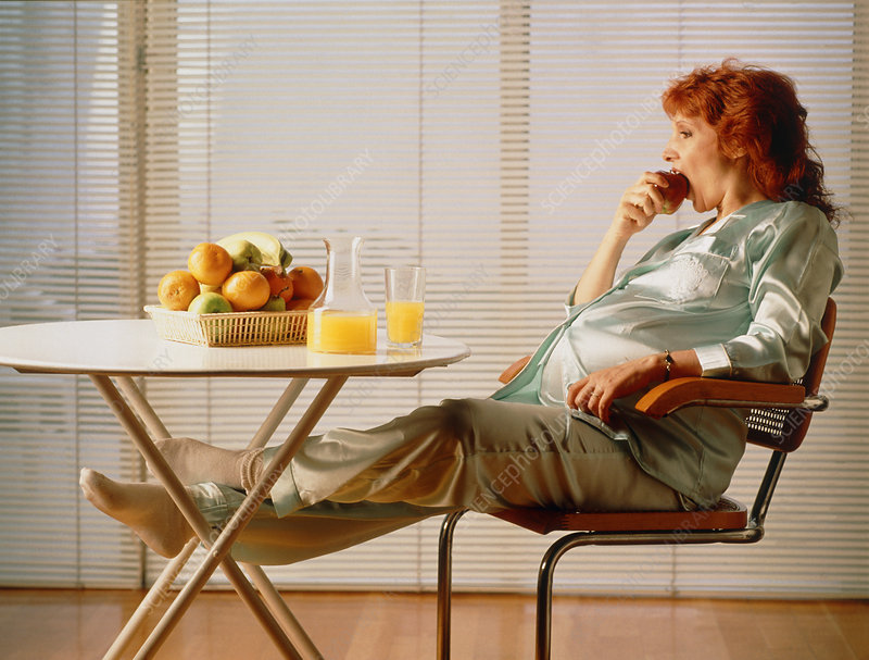Pregnant woman eating apple & drinking fruit juice