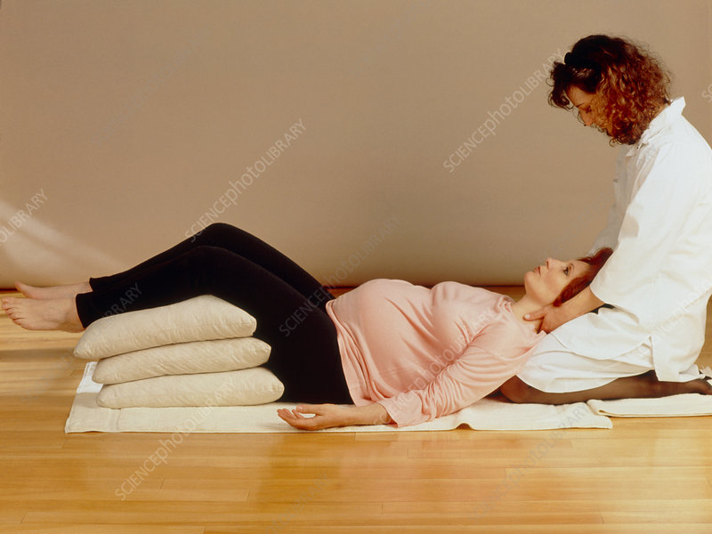 Pregnant woman assisted during prenatal exercise