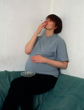 Pregnant woman smoking a cigarette indoors