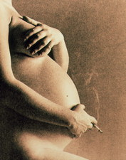 Naked torso of pregnant woman smoking a cigarette