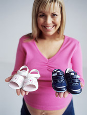 Pregnant woman with baby shoes