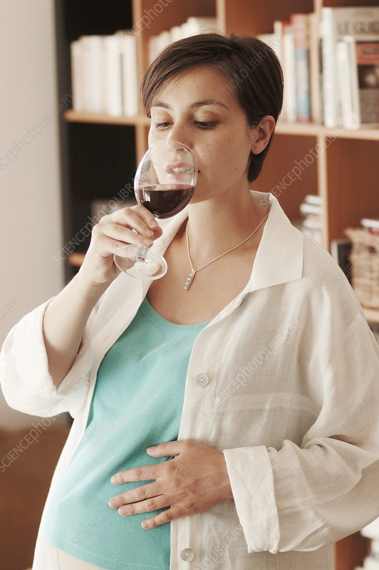 Eight-month pregnant woman drinking wine