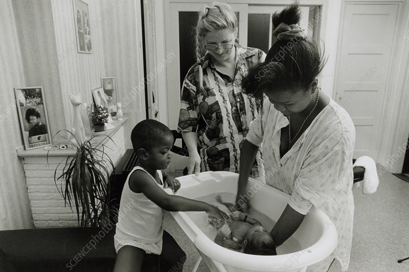 District maternity nurse watches mother bathe baby