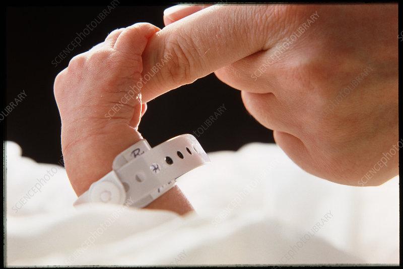 Newborn baby's hand instinctively grasping finger