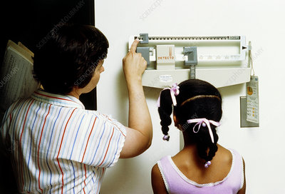 Nurse measures young girl on weighing scales