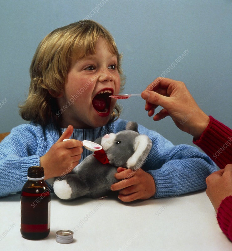 Child receiving a dose of cough mixture