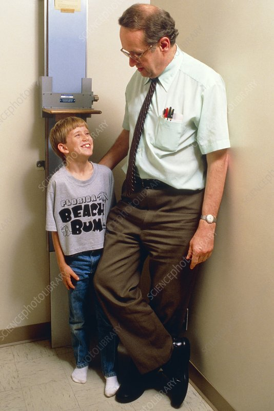 Boy being measured after growth hormone therapy