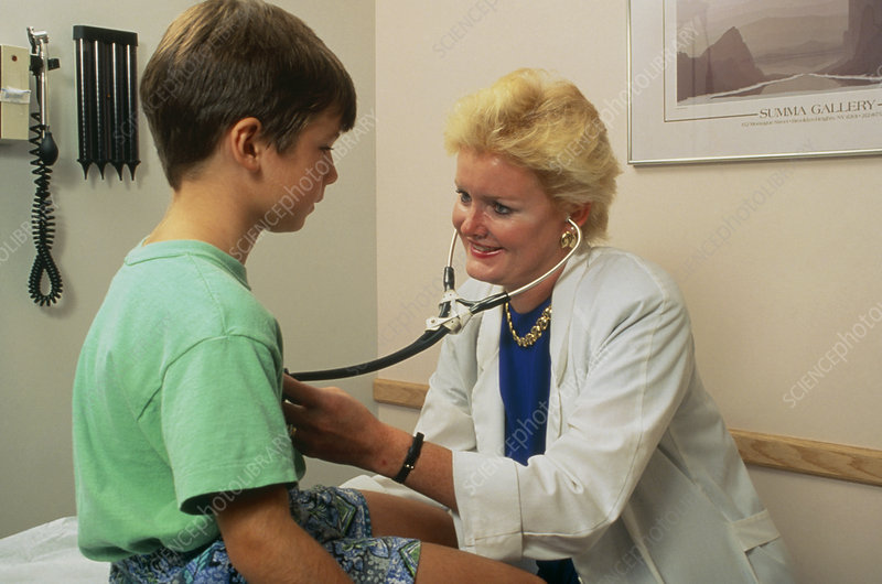 Doctor listening to a young boy's heart and lungs