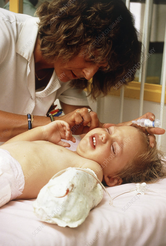 Child being given ear drops by nurse, hospital