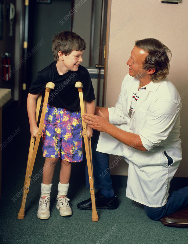 Paediatric doctor reassures young boy on crutches