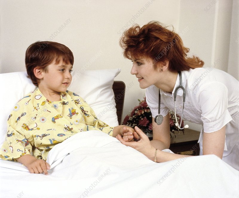 Nurse reassures young boy in a paediatric ward