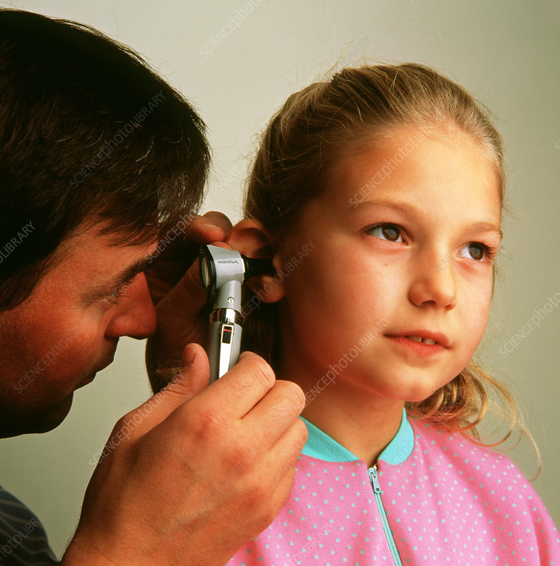 Doctor examines ear of young girl using otoscope