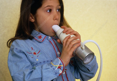 Young asthmatic girl breathes into a vitalograph