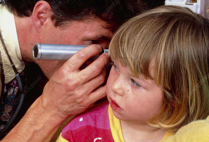 Doctor examines a girl's ear using an otoscope
