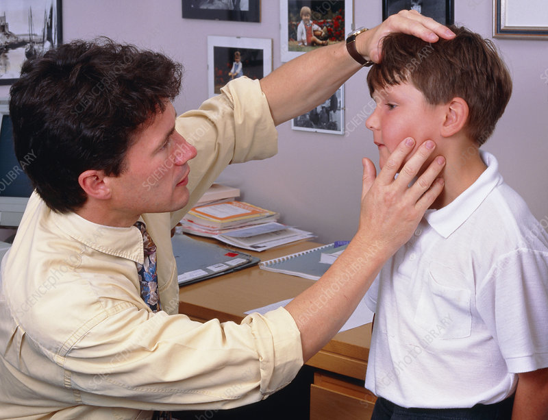 Doctor examines young boy's face and neck