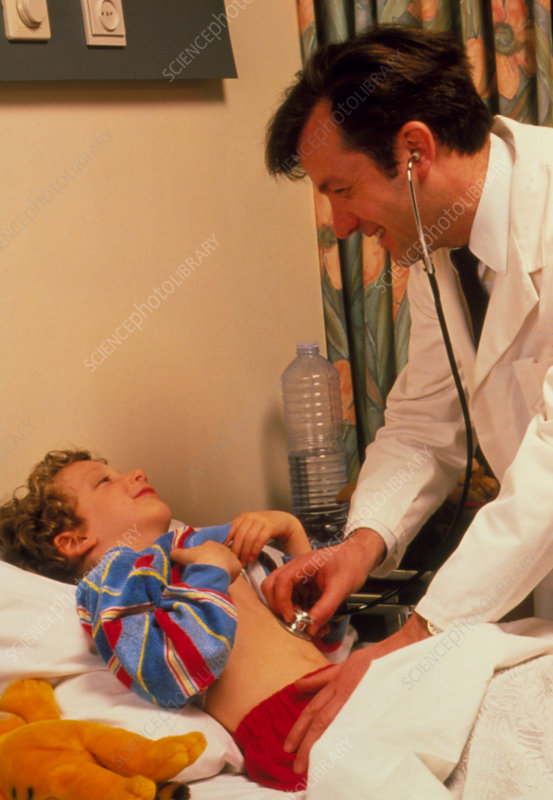 Doctor examining young boy in hospital bed