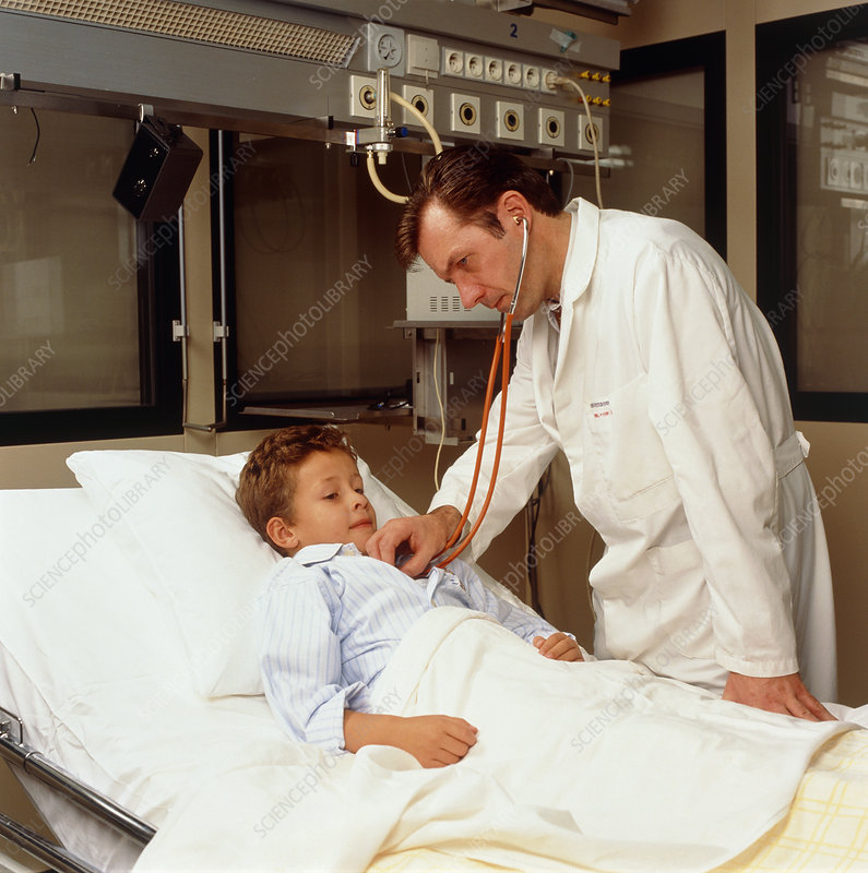 Doctor uses a stethoscope on a boy in hospital