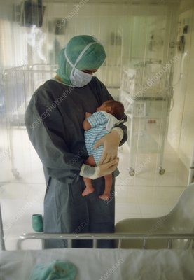 Nurse holds immunodeficient baby in sterile room