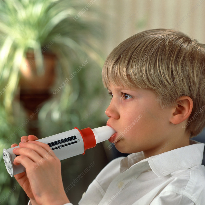 Lung function: boy breathes into peak flow meter