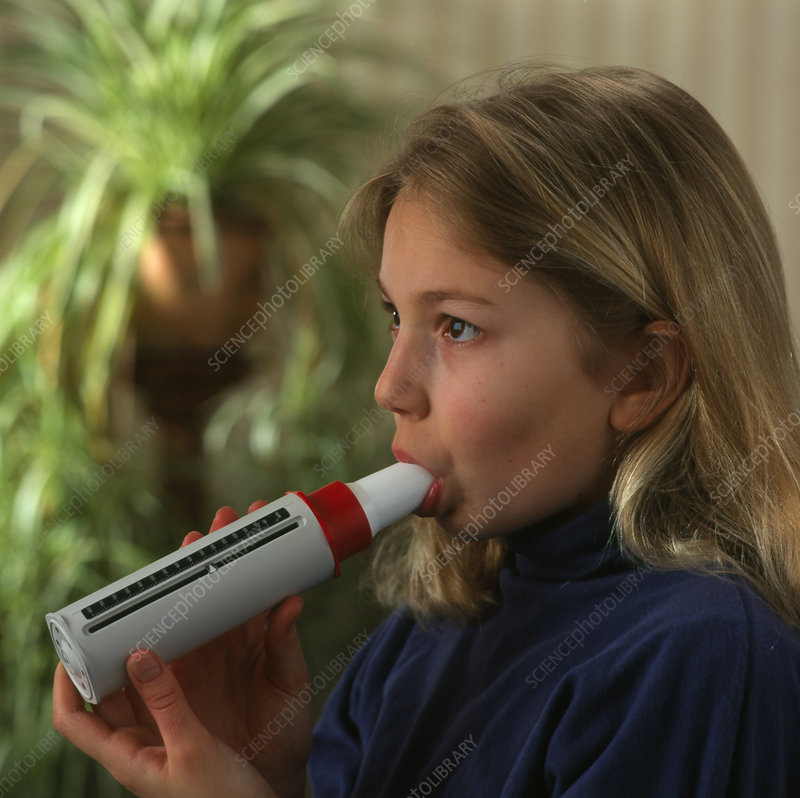 Lung function: girl breathes into peak flow meter