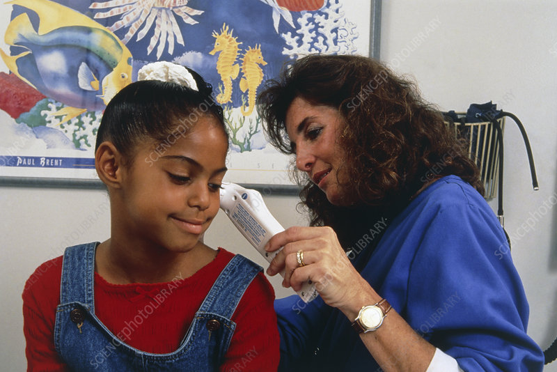 Nurse using digital thermometer in ear of girl