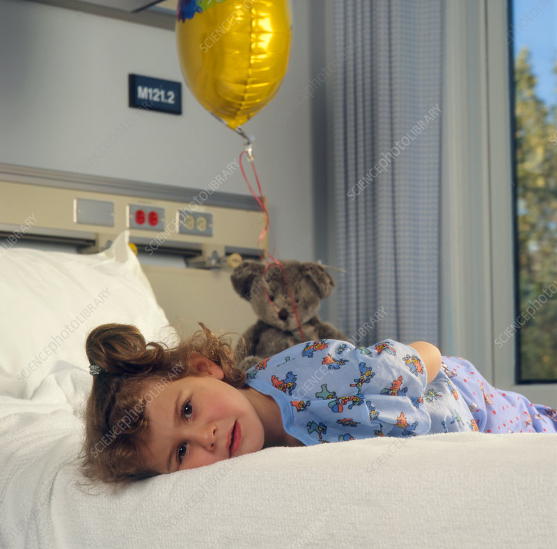 Sad young girl on a bed in a paediatric ward