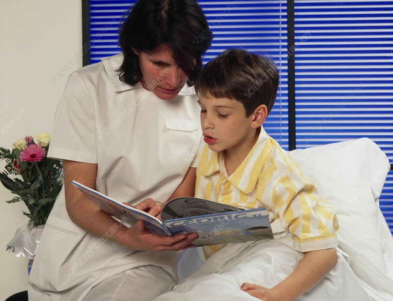 Paediatric nurse reads with a young boy in a ward