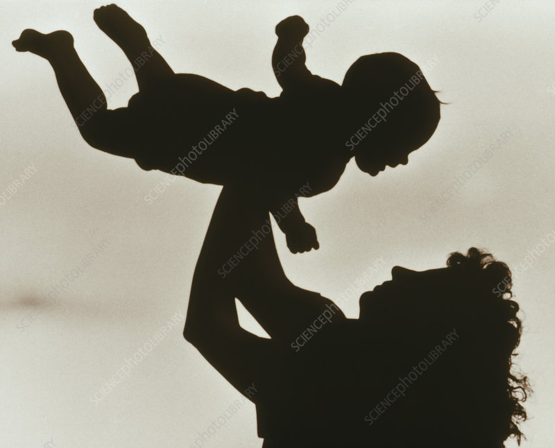 Silhouette of mother throwing baby into the air