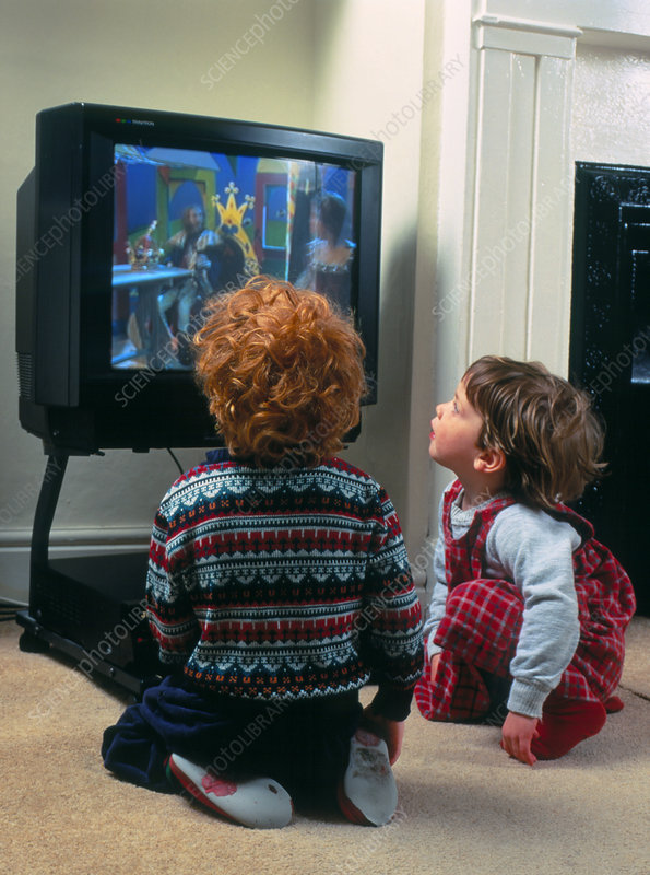 Children closely watching the TV