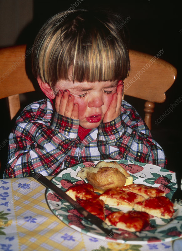 Angry two-year-old boy has a tantrum during dinner