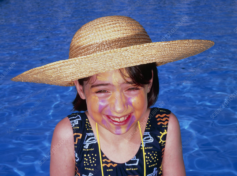 Smiling young girl wearing coloured sunblock