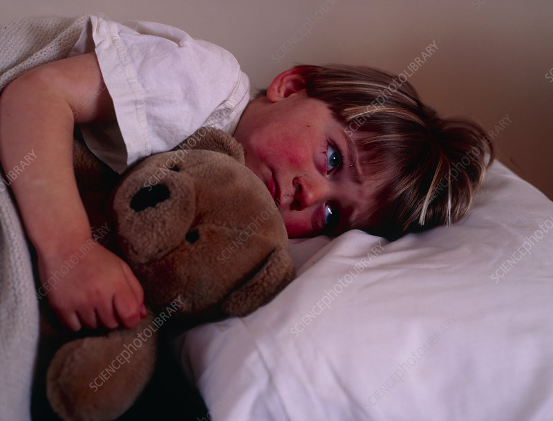 Three year-old child in bed with teddy bear